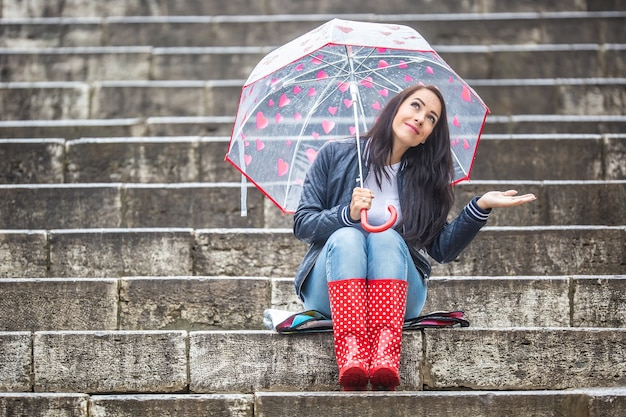 Girl sits on stone stairs outdoors protected by an umbrella, smiling, looking at the sky, checking if it really stopped raining.