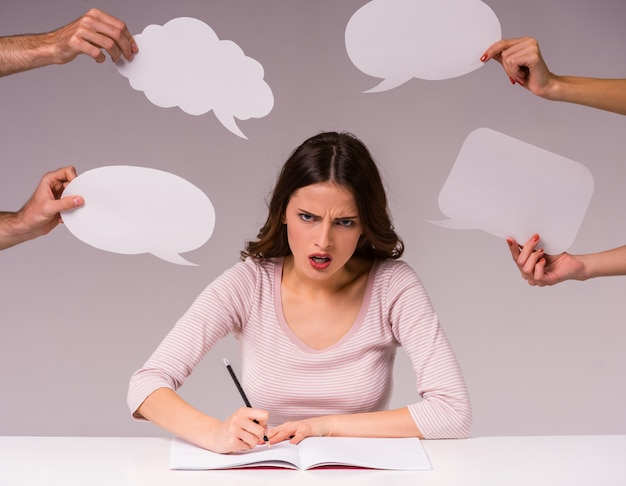 Girl sits at the table and her surrounded by speech bubbles