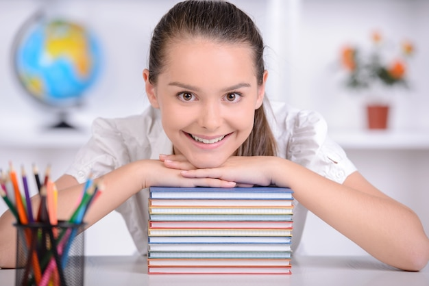 Girl sits at table and put her hands and head on the book.