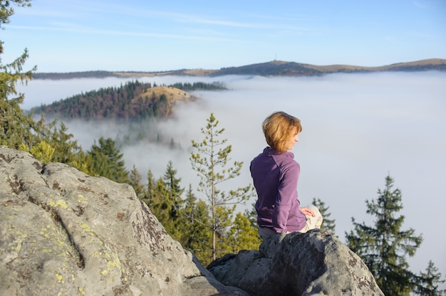 Girl sits on top of a mountain, looking at around