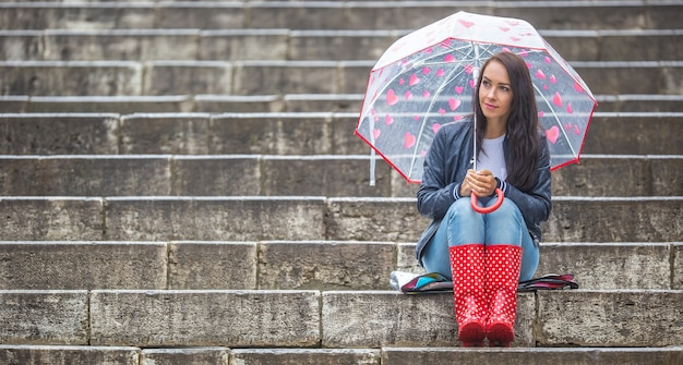 Girl sits waiting on stone stairs, wearing red rain boots and a umbrella with hearts protecting her against the rain.