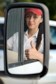 Girl sits behind the wheel and shows thumbs up.