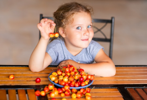 A girl sits at a wooden table and holds a sweet cherry in his hands