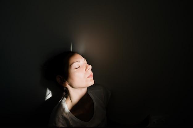 Девушка сидя самостоятельно в кармане солнечного света в темной комнате. концепция психического здоровья