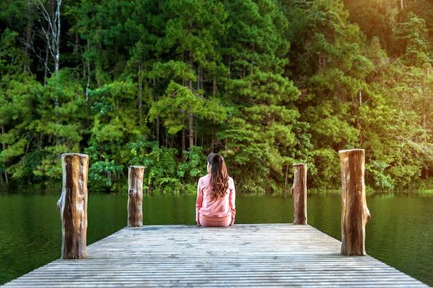 소녀는 호수에 나무 다리에 혼자 앉아. pang ung, 태국.