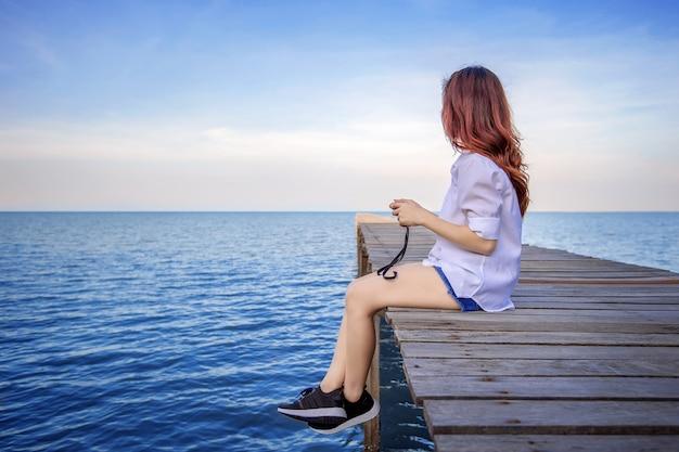 海の上の木製の橋に一人で座っている女の子。ヴィンテージトーンスタイル。