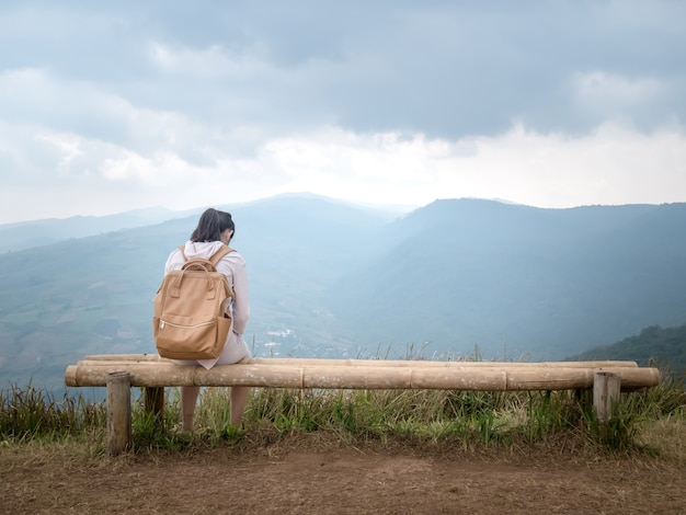 A girl sitting alone and shoulder bag brown. on a long wooden chair at high mountains.