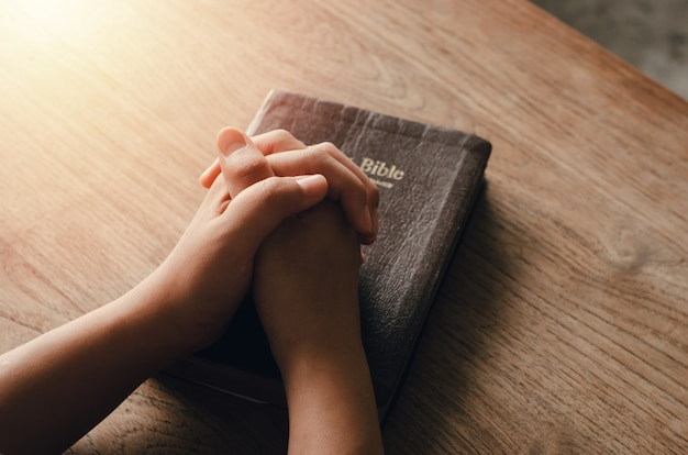 座って神からの祝福を祈る少女聖書は、聖書的、精神的、宗教的な祈りの中で手を組んで、コミュニケーションを取り、神と話します。愛と許し