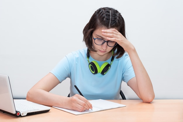 テーブルに座って宿題を書いている女の子。