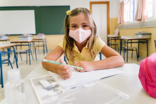 전염병 동안 자신을 보호하기 위해 마스크를 쓰고 교실에서 의자와 테이블에 앉아있는 소녀