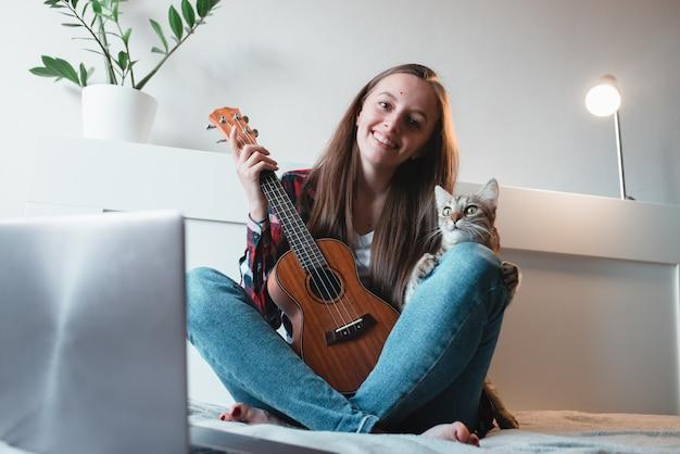 Девочка, сидящая дома, учится играть на укулеле с помощью онлайн-уроков.