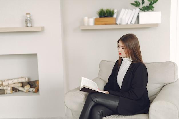 Девушка сидит на стуле и читает книгу