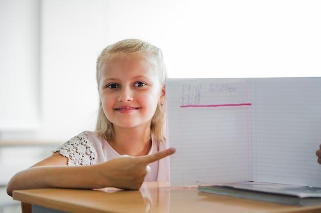 Девочка сидит за школьным столом с ноутбуком