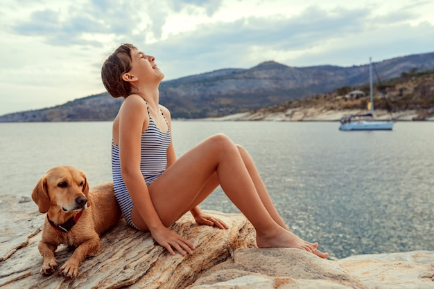 Girl sitting on the beach with dog and laughing
