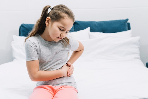 Girl sitting on bed having abdominal pain