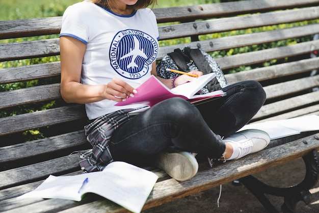 Girl sitting on bench in park studying