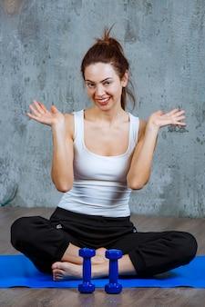Ragazza seduta su un mascherino yoga blu e facendo una pausa.