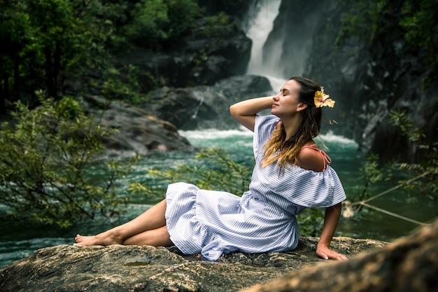 滝のそばに座っている女の子