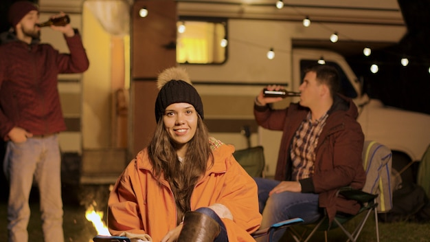 Girl sitting on a camping chair in a cold night of autumn. friends clinking beer bottles in the background.