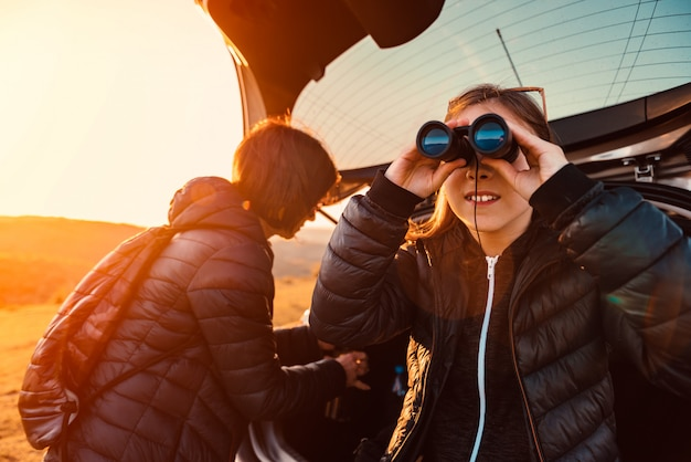 Girl sitting on a car trunk and using binoculars