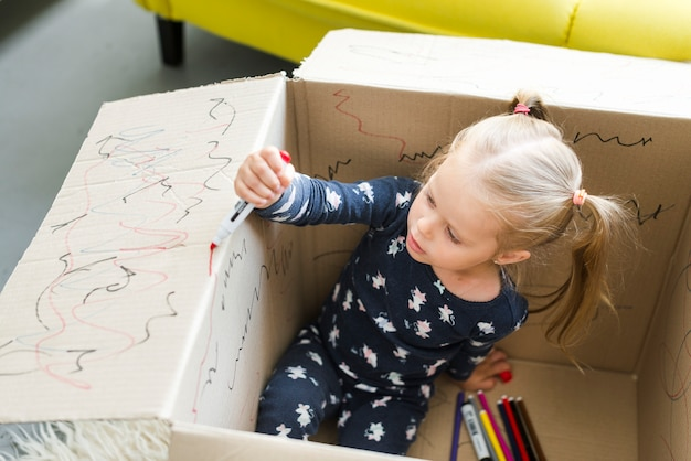 Girl sitting in cardboard box and decorating it with felt tip pen