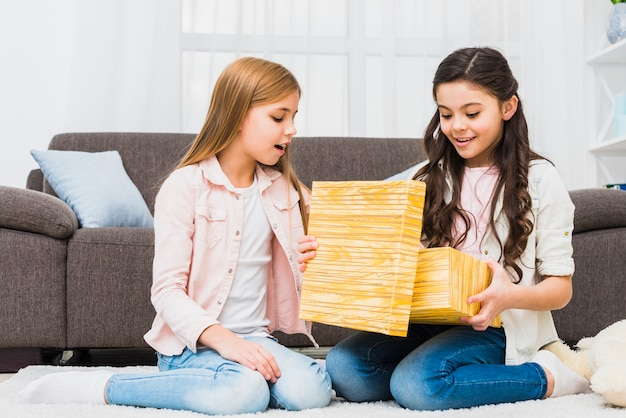 Girl sitting on carpet looking at her friend opening the gift box