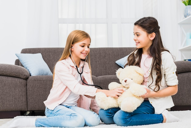 Girl sitting on carpet playing with teddy using stethoscope in the living room