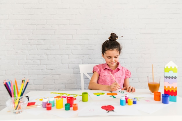 A girl sitting on chair painting on white paper with colorful paint bottle and colored pencils on table