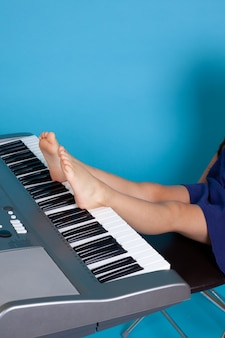 Girl sitting on a chair and playing the piano with her feet