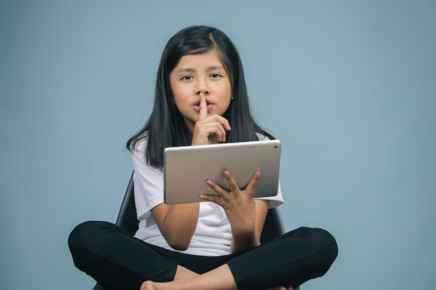 Girl sitting on a chair watching tablet