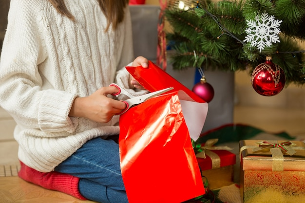Girl sitting under christmas tree and cutting red paper with scissors for decorating presents