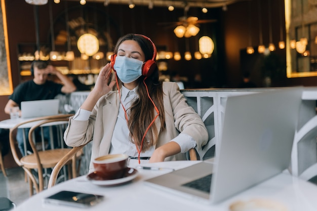 A girl sitting in a coffee shop with headphones coronavirus outbreak