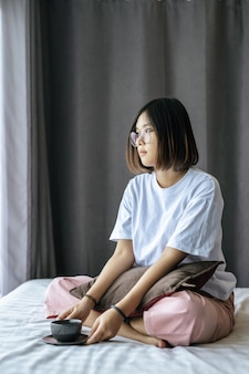 A girl sitting and drinking coffee on the bedroom.