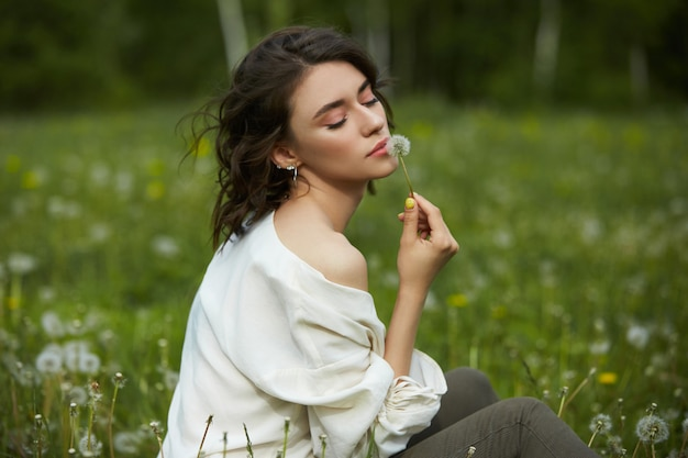 Girl sitting in a field on the spring grass with dandelion flowers