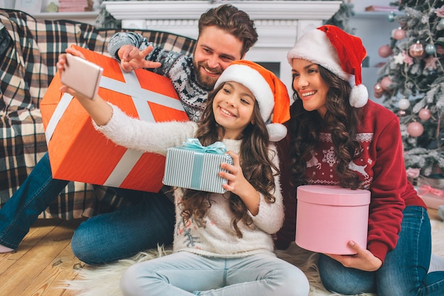 Girl sitting on floor ith her parents and holding phone in hands. she takes picture of them. people posing and smiling. each of them has box of present in hands.