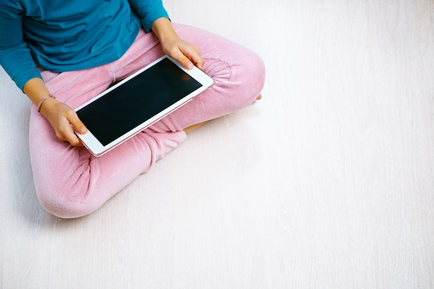 Girl sitting on the floor looking at the tablet with pink trousers and blue shirt