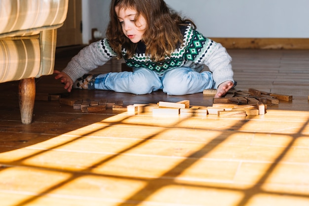 Girl sitting on floor playing with wooden blocks