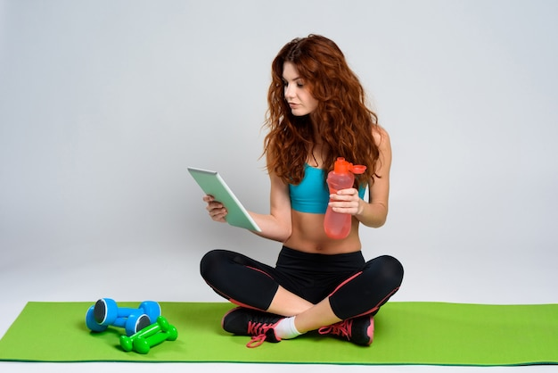 Girl sitting on the floor with tablet and bottle of water.
