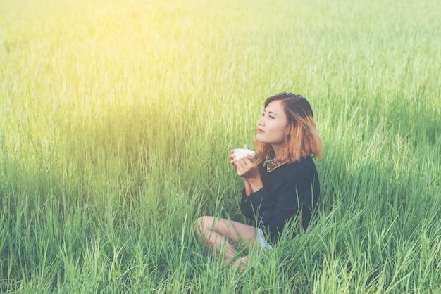 Ragazza che si siede nell'erba