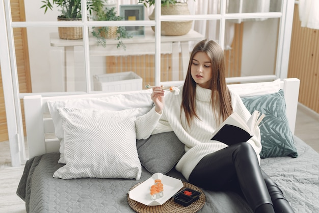 Girl sitting at home at the couch with a sushi
