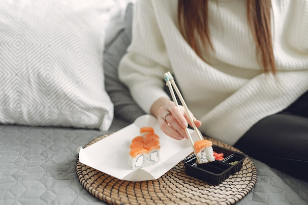 Girl sitting at home on a couch with a sushi