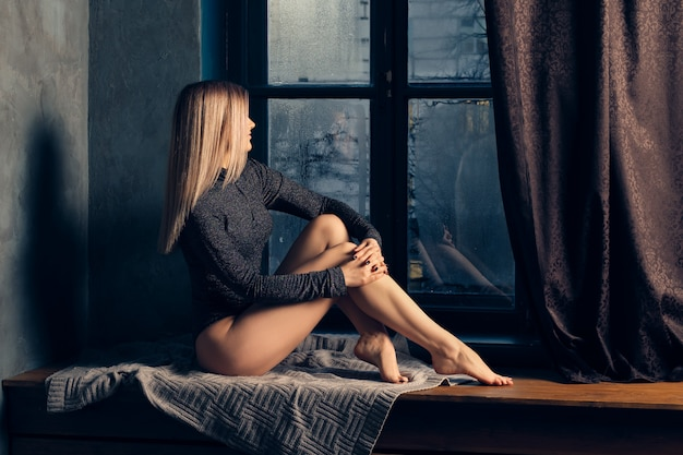Girl sitting at home in rainy evening on window sill