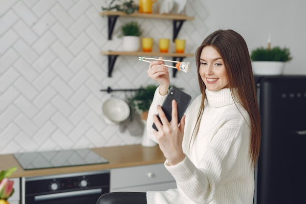 Girl sitting at home at the table with a sushi