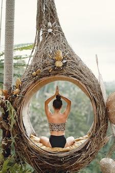 Девушка сидит в большом гнезде на бали