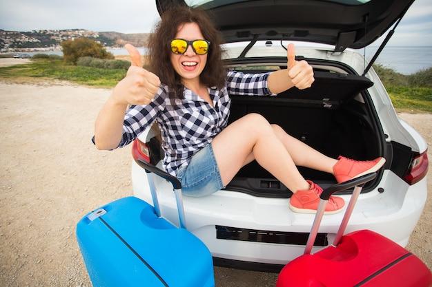 車の後ろに座って笑顔で親指を立てている女の子。車の開いたトランクに座っている若い笑う女性。夏のロードトリップ。
