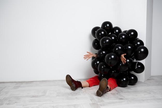 흰 벽 위에 손을 스트레칭 검은 baloons에 앉아 소녀.