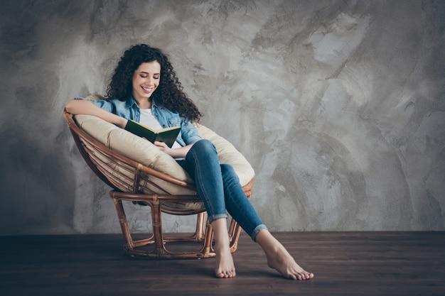 Девушка сидит в кресле, читая роман бумажную книгу в современном интерьере комнаты в индустриальном стиле лофт