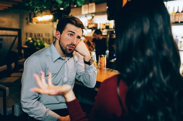 Девушка сидит перед молодым парнем и разговаривает с ним