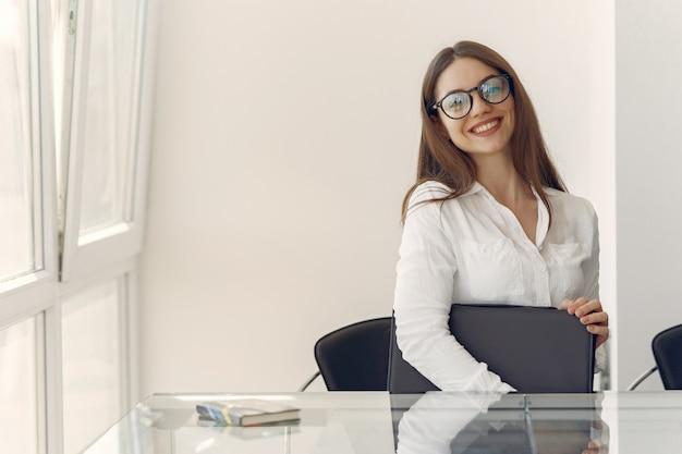 Девушка сидит в офисе с ноутбуком