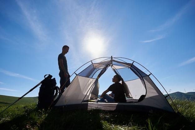 Девушка сидит в палатке и парень стоит вокруг и смотрит на нее на фоне голубого неба с ярким солнцем и зелеными холмами